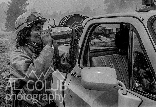 September 1, 1987 Buck Meadows, California -- Stanislaus Complex Fire -- Truxton Canyon Firefighter from Bureau of Indian Affairs takes drink of water before returning to fire camp. The Stanislaus Complex Fire consumed 28 structures and 145,980 acres.  One US Forest Service firefighter, David Ross Erickson, died from a tree-felling accident.