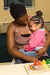 preschool 2-3 year olds separation beginning of school day female teacher comforting sad girl