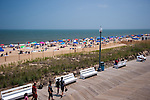 Happy vacationers crowd the beach and walk the boardwalk on the first day of summer at Rehoboth Beach, Delaware.