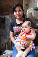 Single mother Josephine Savares, 18, holds her 1st child Jihan, aged 4 months, in her neighbourhood, in Paranaque City, Metro Manila, The Philippines on 19 January 2013. After watching advertisements, Josephine had decided to feed her baby formula during her pregnancy and had no idea that her father had to pay such a high price for it. Her family goes without food some days, and her siblings have had to stop school in order to afford the formula. Photo by Suzanne Lee for Save the Children UK