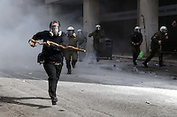 Pictured: A farmer with a stick is chased by riot police officers Friday 12 February 2016<br /> Re: Violent clashes between farmers and riot police outside the Ministry of Agricultural Development in Athens, Greece. The farmers travelled from Crete to protest against pension and welfrae reforms proposed by the Greek government,