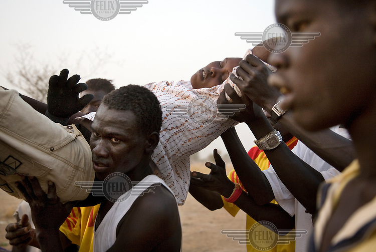 A young woman is carried away by her victorious football team after fainting with joy at their success at the Twic Olympics in Wunrok, Southern Sudan.