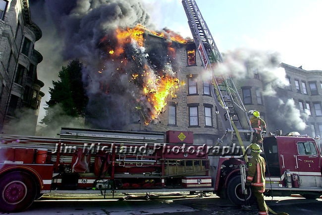 A large burning  section of the top floor collapses during a multi alarm fire in downtown Holyoke Ma Saturday afternoon, fire depts from several towns assisted the Holyoke Dept in battling the blaze in the large U shaped apartment block for hours as many as 125 people were left homeless, no injuries were reported. A Jim Michaud pic 2/3/01