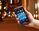 Hand with Blackberry Z10 smartphone outside on a city street at night