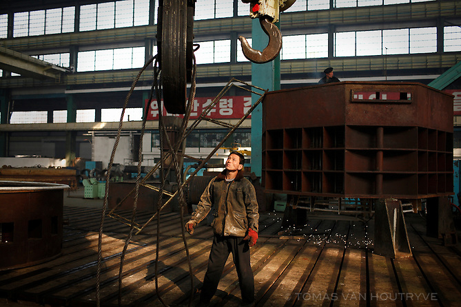 A Korean factory worker looks up at a crane inside a metal fabrication factory on the outskirts of Pyongyang, North Korea (DPRK) on 29 February 2008.