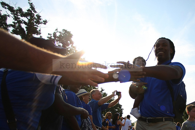 Kentucky defensive end Za'Darius Smith (94) and his son Zaiden Smith high fives a fan prior to the game between the University of Kentucky vs. University of Tennessee Martin football game at Commonwealth Stadium in Lexington, Ky., on Saturday, August 30, 2014. Photo by Michael Reaves | Staff
