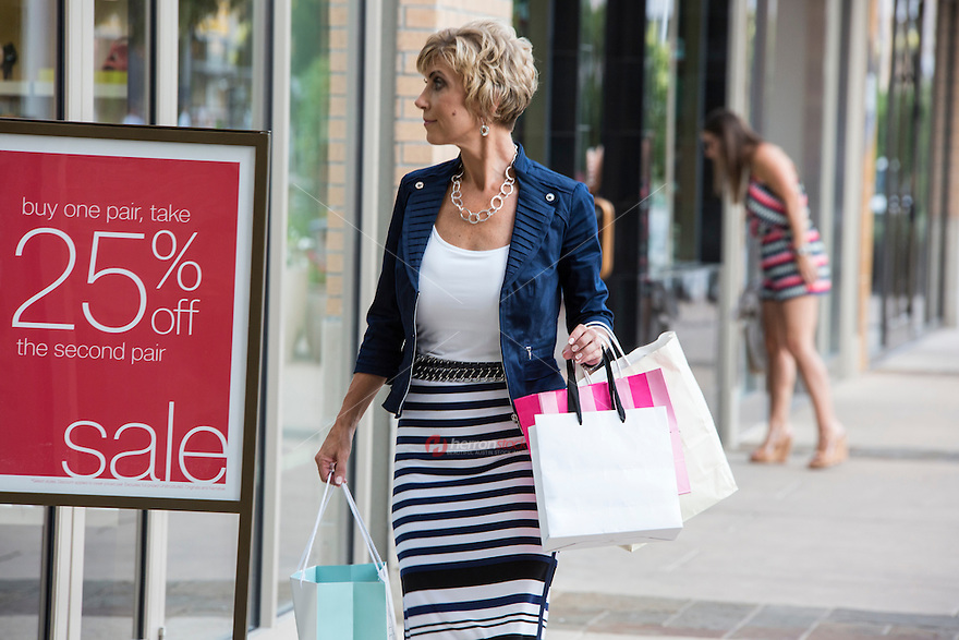 Elegant female mall shopper with shopping bags window shops at a popular Austin outdoor shopping center