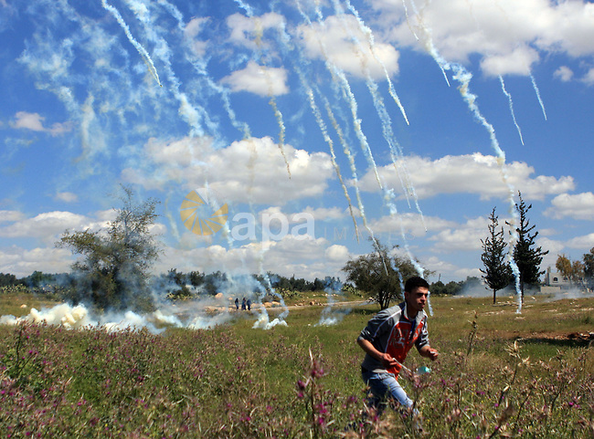 A Palestinian demonstrator runs to take cover from tear gas canisters fired by Israeli soldiers during a demonstration marking Land Day and protesting against Israel's separation barrier, in the West Bank village of Budrus, near Ramallah, Tuesday, March 30, 2010. Land Day commemorates the killing of six Arab citizens of Israel by the Israeli army and police on March 30, 1976 during protests over Israeli confiscations of Arab land. Photo by Issam Rimawi