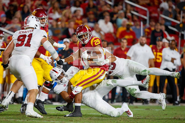 LOS ANGELES, CA - SEPTEMBER 8: USC Trojans running back Vavae Malepeai #29 is tackled by Stanford Cardinal linebacker Jordan Fox #10 and linebacker Andrew Pryts #25 during a game between USC and Stanford Football at Los Angeles Memorial Coliseum on September 7, 2019 in Los Angeles, California.
