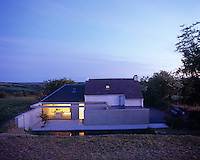 The exterior of the cottage with its minimal concrete converted cowshed at dusk