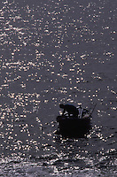 Silhouette of fisherman man in boat, Los Abrigos, Tenerife, Canary Islands.