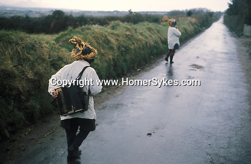 Biddy Boys 1970s. Killorglin, Co Kerry Ireland. February 2nd festival to celebrate the Celtic Saint Bridgid. Two young Biddy Boys - broter and sister - walking from house to house wearing the traditional straw conical hat collecting money.