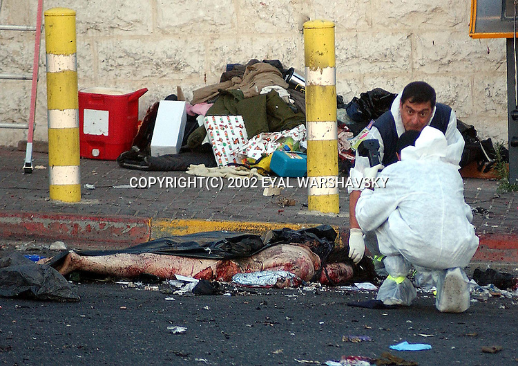 Israeli police officers photograph a body of a woman at the site of a suicide bombing in Jerusalem Wednesday June 19 2002. A suicide bomber exploded at a bus station wednesday killing seven and wounding 40 Photo by Eyal Warshavsky