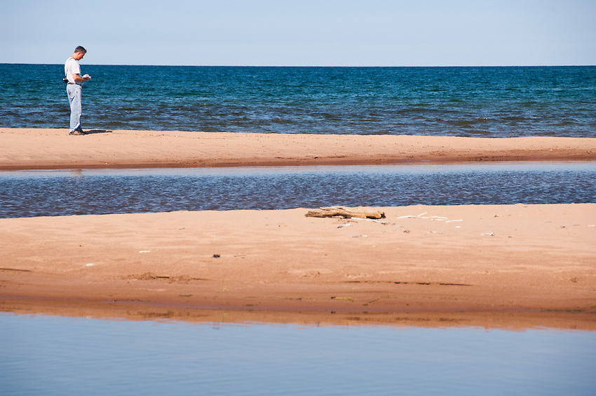 A man walks the Lake Superior beach at the mouth of the Salmon Trout River near Big Bay Michigan.