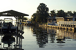 The still water reflects the docks and boats lining a residential canal on Merritt Island, Florida.