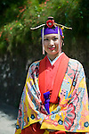 Dressed in traditional garb staffer Maki Takayama stands at the entrance to the grounds of Shuri-jo Castle in Naha, Okinawa Prefecture, Japan, on June 24, 2012. Photographer: Robert Gilhooly