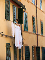 Woman hanging laundry outside apartment window on clothes line attached to side of building, Siena, Ital