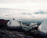 GREENLAND, Ilulissat, Disco Bay, elevated view of Hotel Arctic with icebergs and the sea in the background
