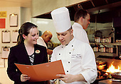Hotel & Management student on work placement in London hotel discussing the menu with the chef.