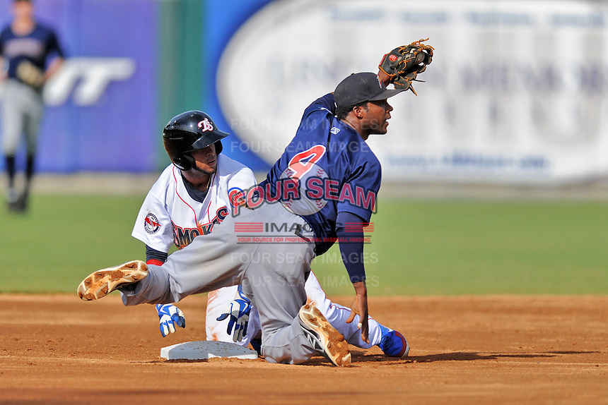 Huntsville Stars shortstop Hector Gomez #4 fields the ball and puts the tag on the hard sliding Rubi Silva #24  of the Tennessee Smokies during game one of a double header at Smokies Park on July 8, 2013 in Kodak, Tennessee. The Stars won the game 2-0. (Tony Farlow/Four Seam Images)