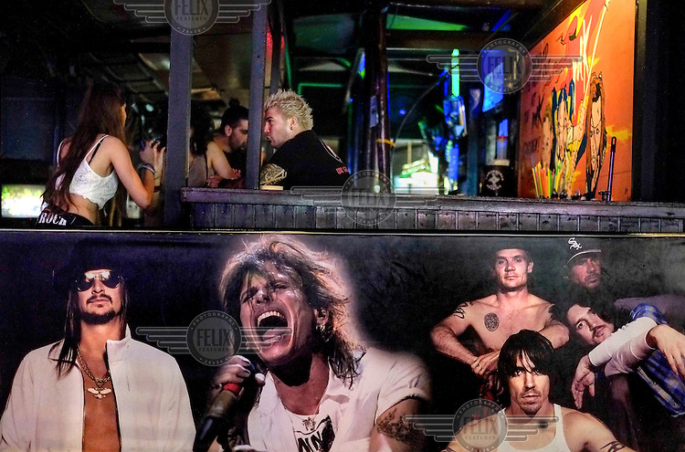 A bar, decorated with pictures of rock stars, in a club.