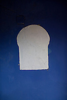A white window shaped shape on a blue painted wall