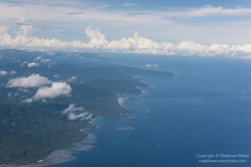 Guadalcanal, Solomon Islands; an aerial view of the western coastline of Guadalcanal Island with white puffy clouds overhead