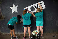"Members create a mural under a train bridge during ""Circle the City with Service,"" the Kiwanis Circle K International's 2015 Large Scale Service Project, on Wednesday, June 24, 2015, in Indianapolis. (Photo by James Brosher)"