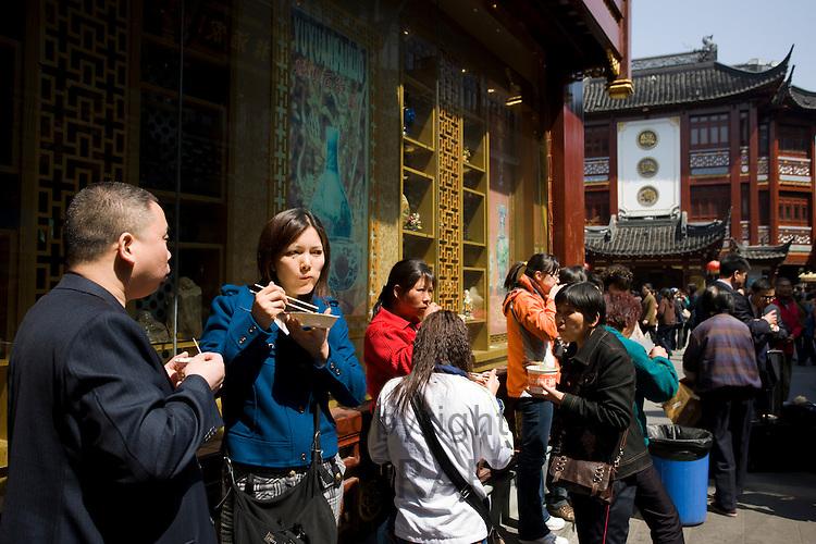 People eating street food in the Yu Garden Bazaar Market, Shanghai, China