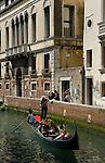 Venice-Italy - March 28, 2010 -- A gondola / gondolier with passengers / tourists glides through a small canal -- infrastructure, transport, water -- Photo: © HorstWagner.eu