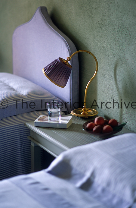A small brass bedside lamp with a purple shade matches the purple headboards of a pair of twin beds