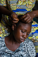 Africa, DRC, Democratic Republic of the Congo, Goma, Lake Kivu,  Global Fund for Women project. PAIF organization safe house shelter for women in Mugunga. The land was bought with GFW grant. Kahindo Kanyeret, lived as a displaced refugee for years in Uganda, with 8 children no husband. She learns to braid hair as a source of income and practices on 15 year old Ndole Jeanette. It's also a way to make women feel beautiful again after the demeaning horrors of being raped.