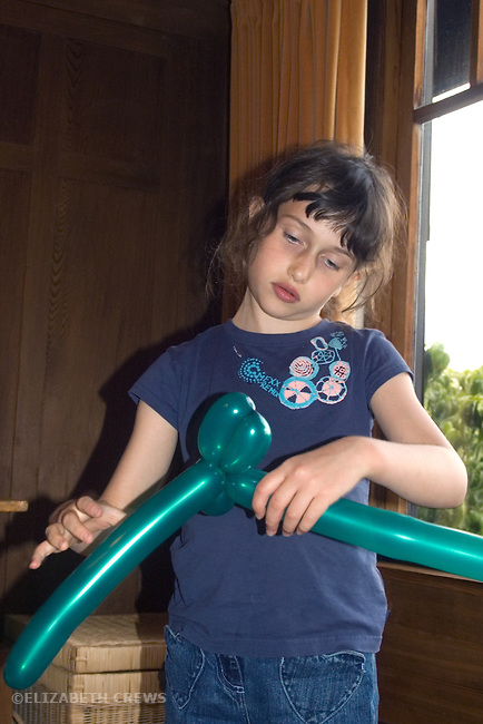 Berkeley CA Girl, six-years-old, mastering the making of balloon animals  MR
