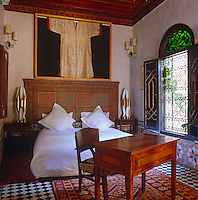 A gold Moroccan djellaba hangs above the bed in a bedroom furnished with an inlaid desk and a pair of retro table lamps