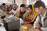 Barefoot College solar technology training for international students selected from villages in Afghanistan (two men in foreground), Ghana (woman centre) and Bolivia (woman with hat and man in background). They will then take the skills they have learned back to villages in their own countries to set up rural solar energy projects. Their teacher is Chagani Devi (woman in foreground), an activist and solar engineering instructor (also trained by the Barefoot College)...
