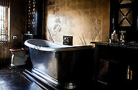 Conventional bath taps have been dispensed with in this glamorous Oriental bathroom, in favour of a gilded lion's head