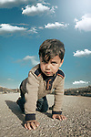 A boy crawls on his hands and feet an looking to camera. Photo by Sanad Ltefa
