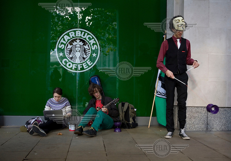 Occupy London protestors outside a Starbucks cafe near St Paul's Cathedral in the City of London using a laptop, playing a guitar and practicing tricks. The protest is part of a worldwide movement against the banking industry and the prevailing economic system..