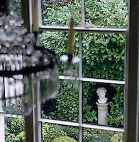 A classical sculpture in the garden seen from the sash window of the stairwell