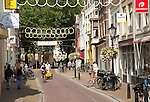 People walking and cycling in historic street central Utrecht, Netherlands