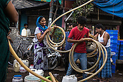 Residents pack their pipes after emptying out the water tanker in the slums of Govind Puri in New Delhi, India. During the peak summer season, the Delhi Jal Board distributes multiple water tankers to the residents in the slum area. Photo: Sanjit Das for The Foreign Policy