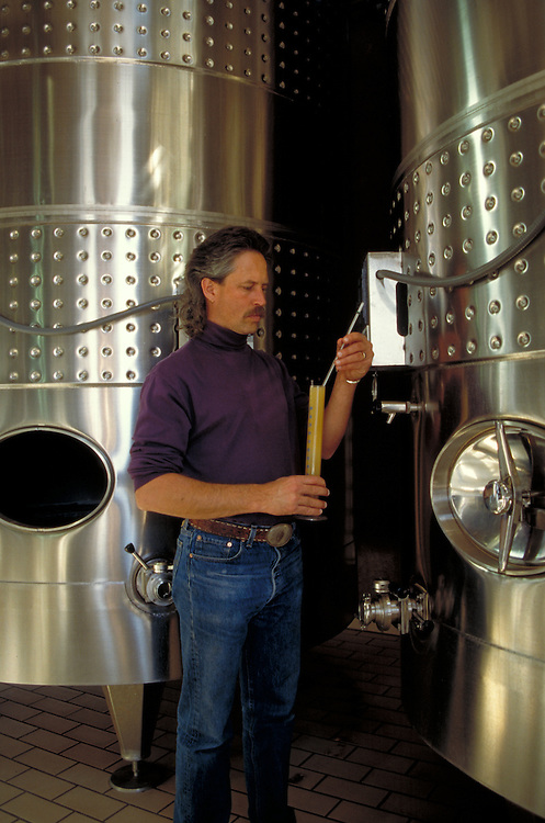 Wine maker Tex Sawyer testing fermentation of new wine in tanks.
