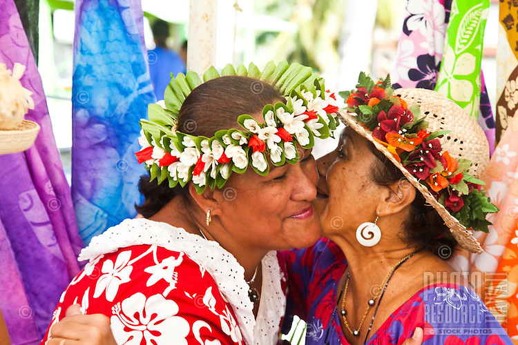 Two Tahitian women greet with a kiss