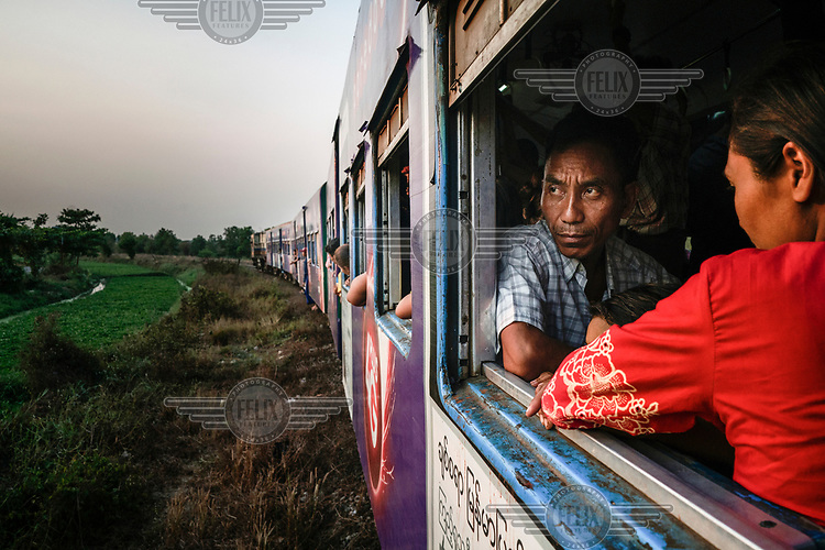 Passengers look out from a carriage on a Yangon Circle Line train as it passes through rural farmland in the north of Yangon. Each day, around 100,000 people use the route despite its antiquated rolling stock and infrastructure. The commuter line loops around the city stopping at 38 stations and taking just under three hours to complete the 45 km (28 miles) circle.