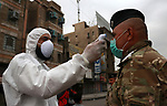 A Iraqi doctor uses a temperature test machine, for a medical examination to detect coronavirus disease (COVID-19) in Baghdad, Iraq, on March 20, 2020. Anas Jomaa
