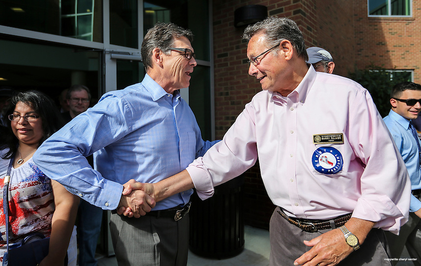 Presidential hopeful former Texas Gov. Rick Perry, left, shakes NH State Rep. Barry Palmer's, right, hand at a cookout and rally at the Nashua Community College in Nashua, N.H.<br /> Former Texas Gov. Rick Perry has opened his second bid for the Republican presidential nomination pledging to &quot;end an era of failed leadership&quot;.   Sunday, June 7, 2015. (AP Photo/Cheryl Senter)