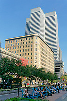 People sitting outdoors on McGill College Avenue with Confederation Building and Place Ville Marie office tower in back, Montreal, Quebec, Canada
