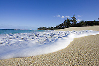 Frothy whitewater washes ashore at Sunset Beach on the North shore of Oahu, Hawaii.