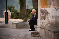 An elderly man sits on the corner of a street in an Italy city