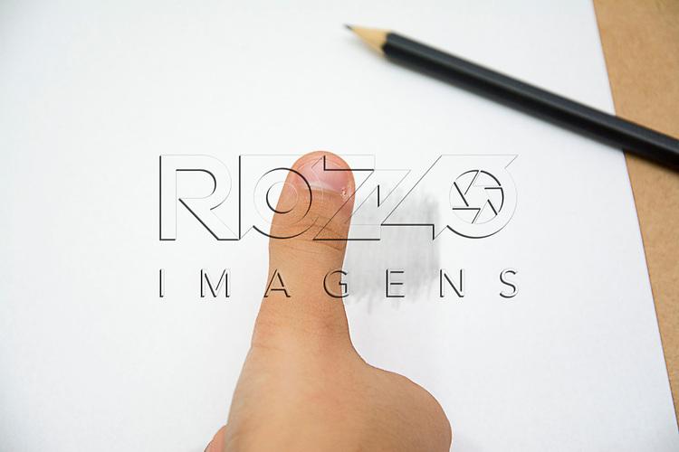 Mão de criança aproximando o polegar direito em uma área de uma folha de papel branca previamente pintada com lápis grafite, São Paulo - SP,12/2015